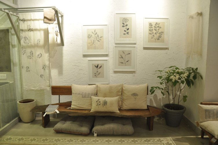 wooden sofa with cushions and white walls with paintings